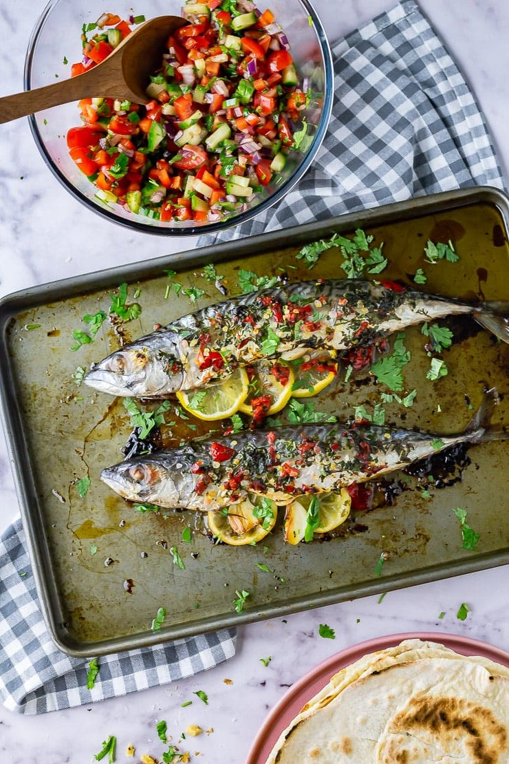 Overhead shot of whole baked mackerel on a baking sheet with a checked cloth