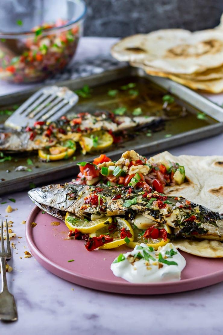 Whole baked mackerel on a pink plate with salad and flatbread