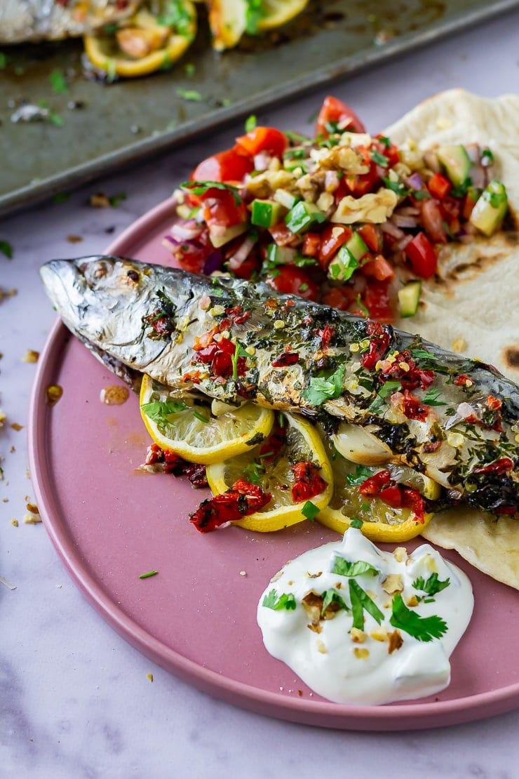 Baked mackerel on a pink plate on a marble background