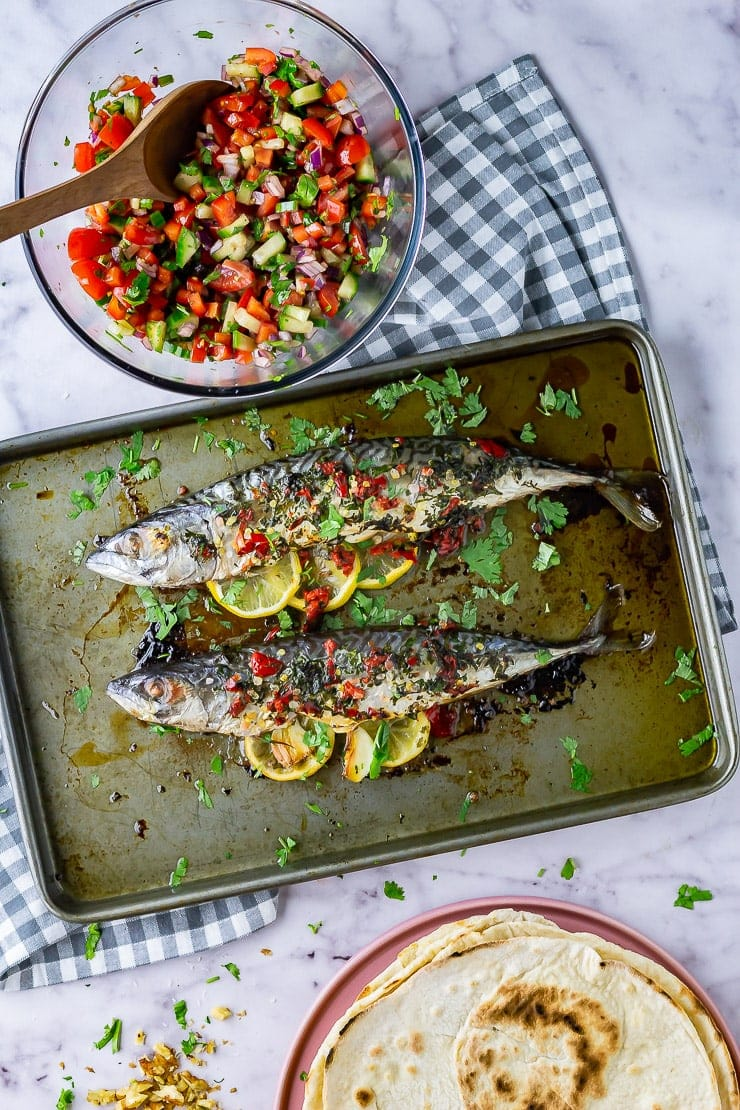 Overhead shot of baked mackerel on a baking sheet on a checked cloth and marble background