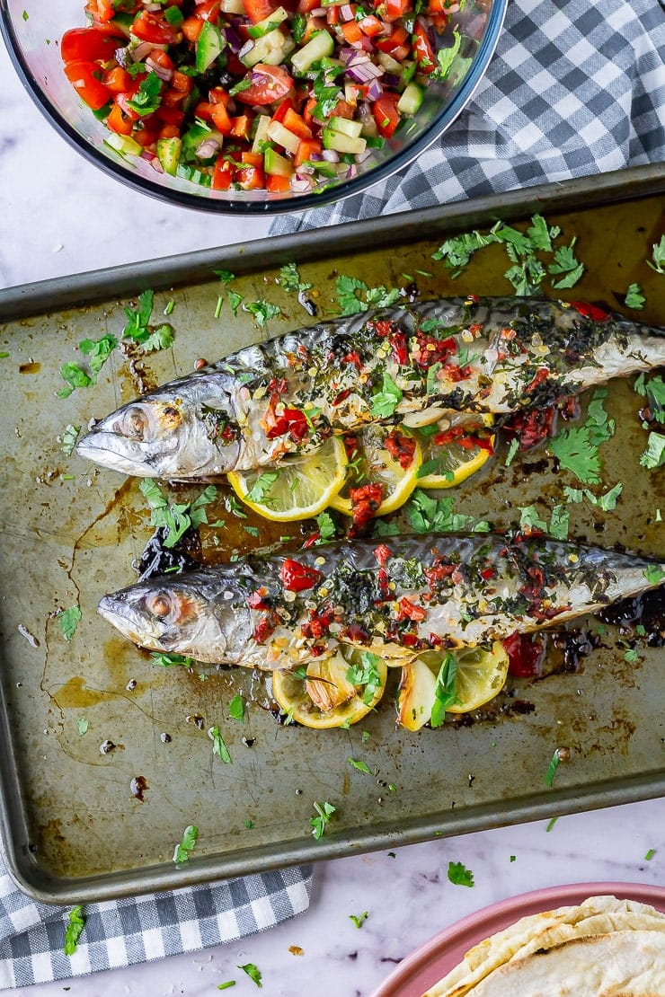 Overhead shot of baked mackerel on a baking sheet on a marble background