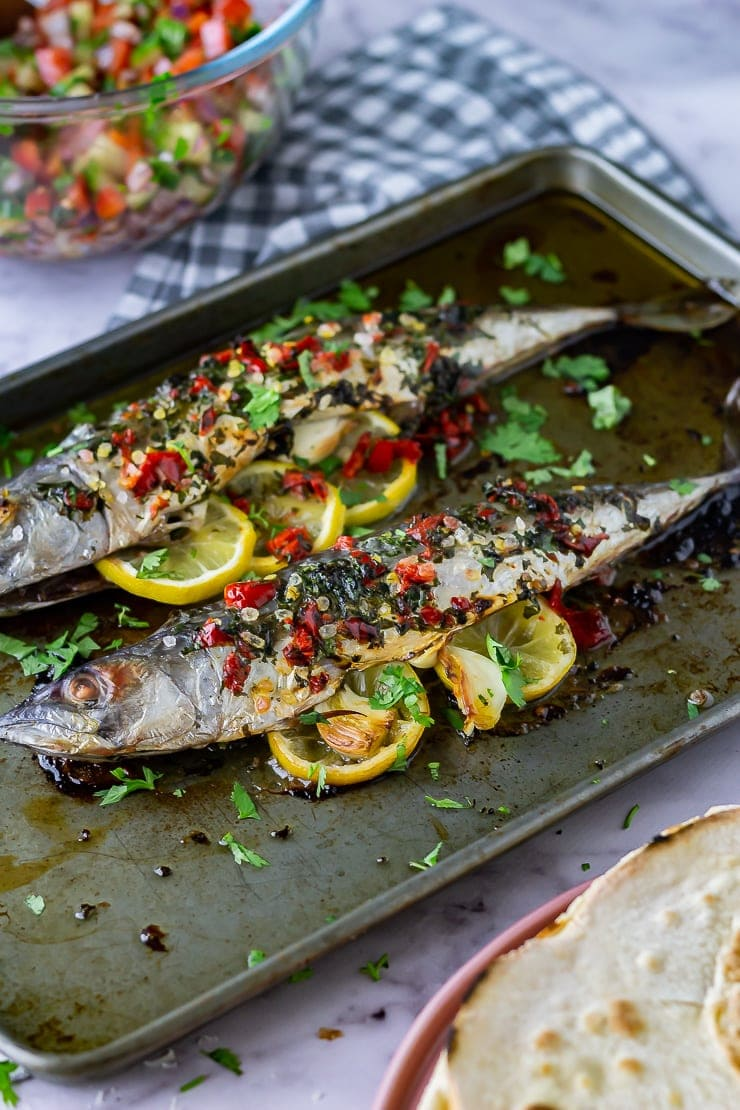 Side on shot of baked mackerel on a baking sheet with a checked cloth