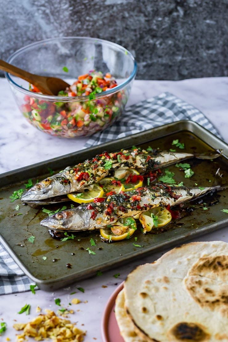 Zoomed out shot of baked mackerel on a baking sheet with salad and flatbreads