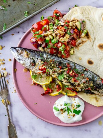 Baked mackerel on a pink plate with salad and flatbread
