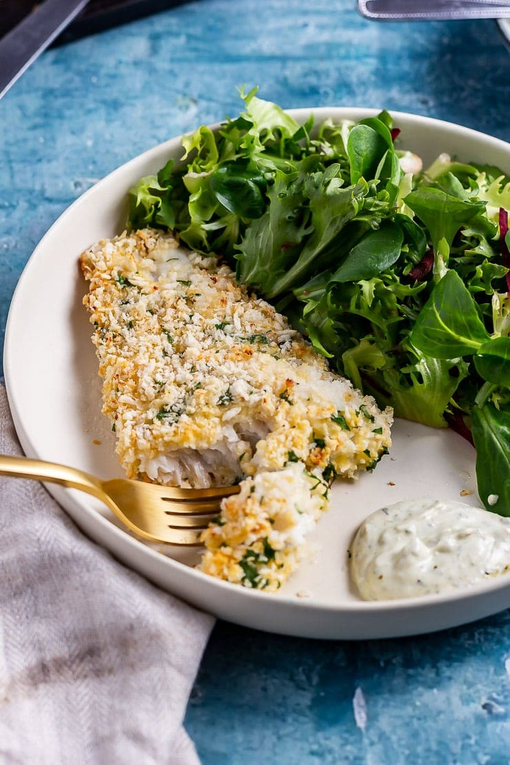 Gold fork cutting into breaded fish with salad in a white bowl