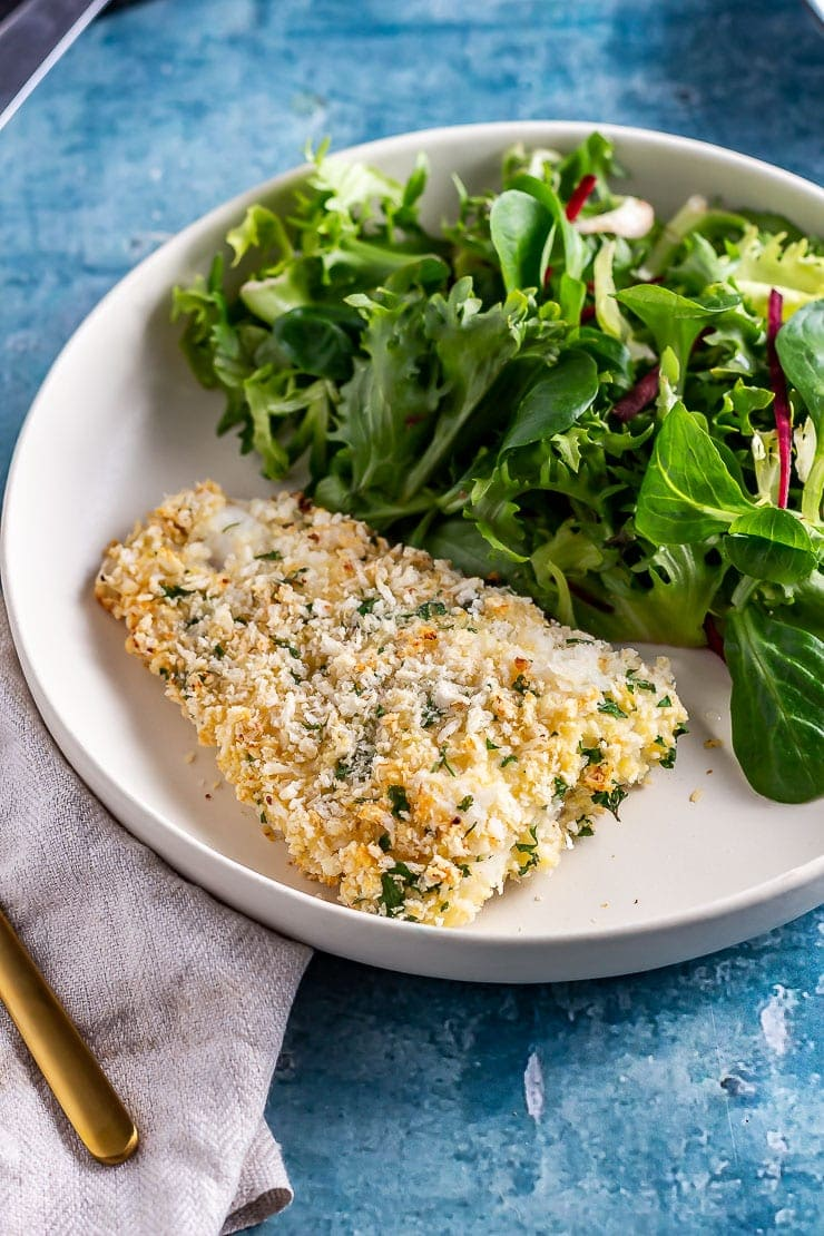 Side on shot of parmesan breaded fish with salad on a white plate over a blue background