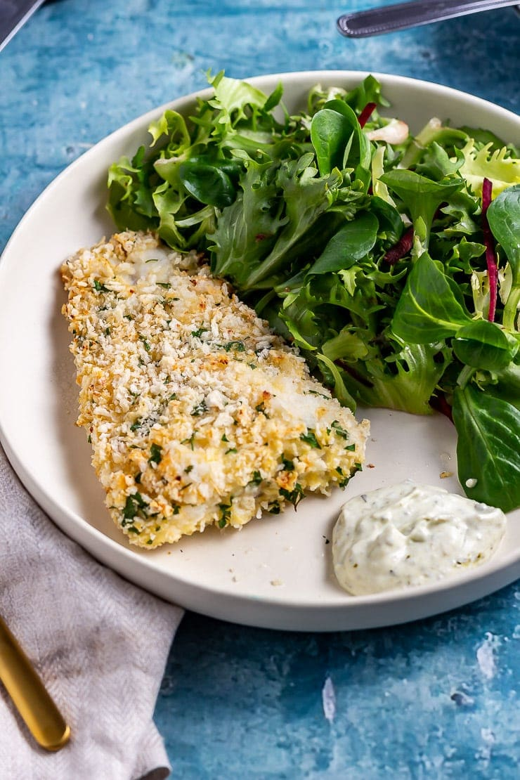 Parmesan breaded fish with salad on a white plate on a blue background