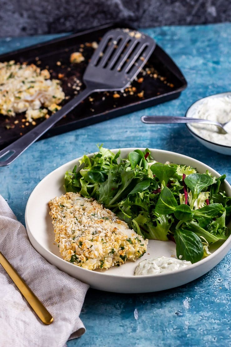 Parmesan breaded fish in a white bowl with salad on a blue background