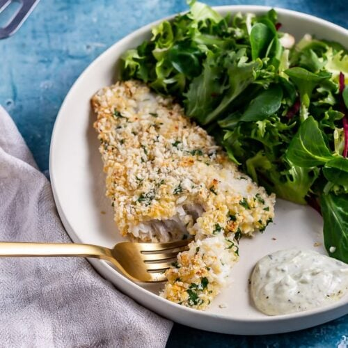 A gold fork cutting into parmesan breaded fish on a white plate with salad and dip