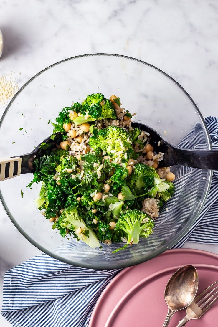 Overhead shot of broccoli and wild rice salad in a glass bowl with salad servers