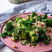 Side on shot of broccoli and wild rice salad on a pink plate on a marble background