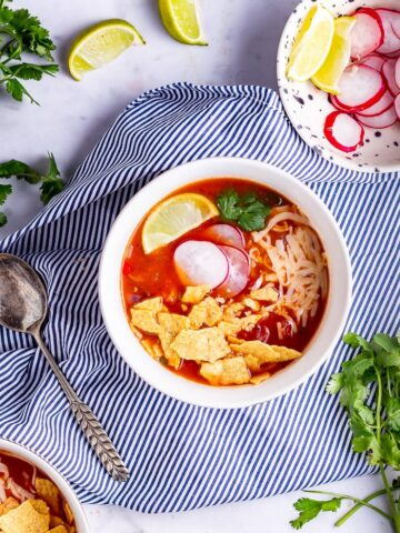 Overhead shot of spicy soup on a striped cloth with lime and coriander