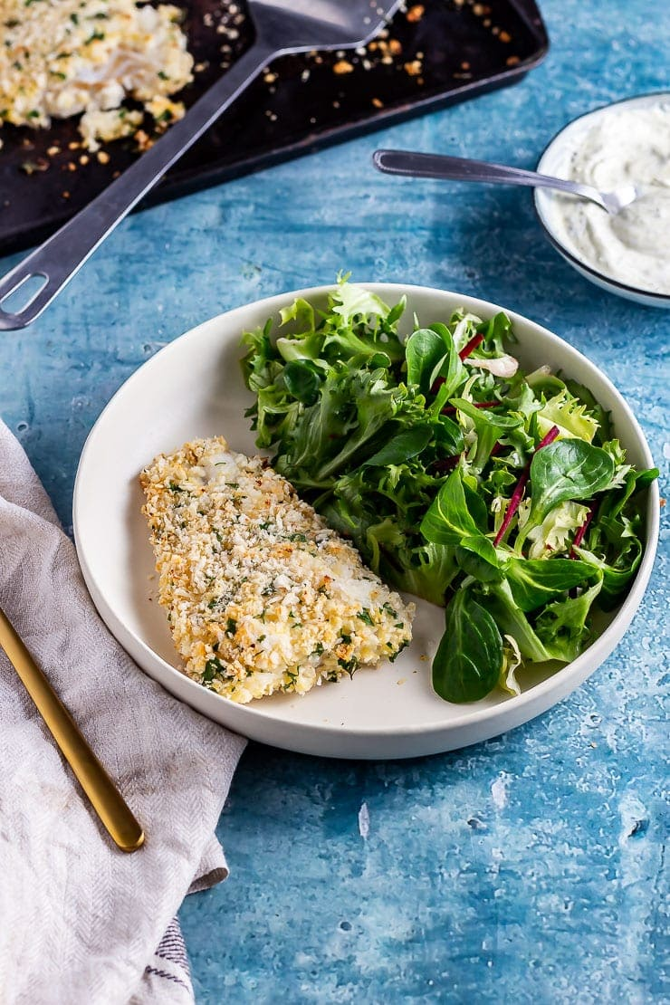 Parmesan breaded fish with salad in a white bowl on a blue background