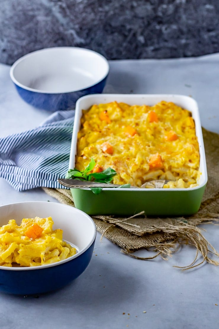 Sweet potato mac and cheese in a green baking dish with a portion taken