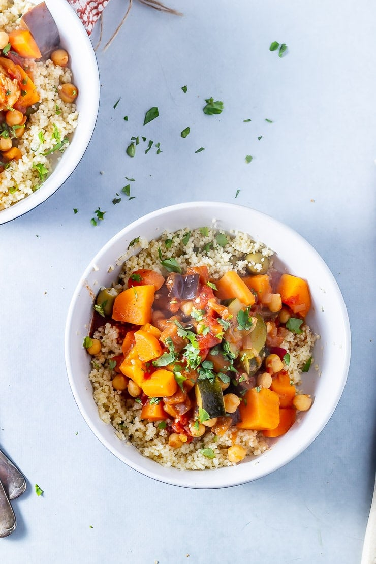Overhead shot of vegetable tagine with couscous in a white bowl of a grey background