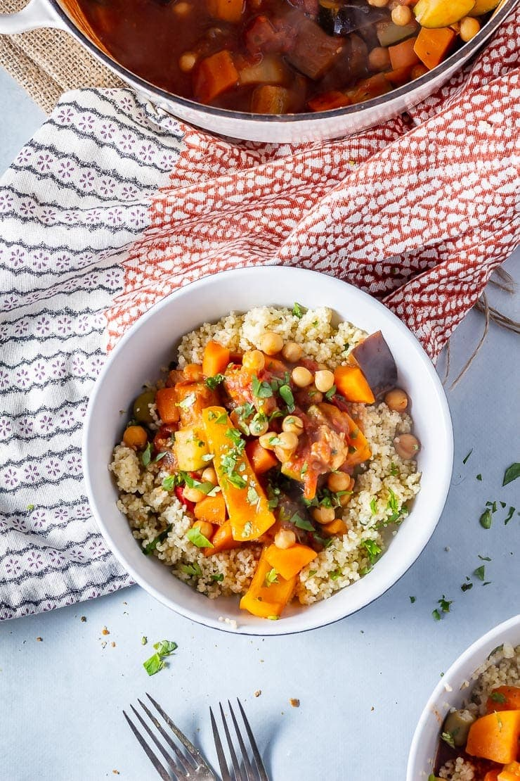 Overhead shot of vegetable tagine with couscous in a bowl on a grey background