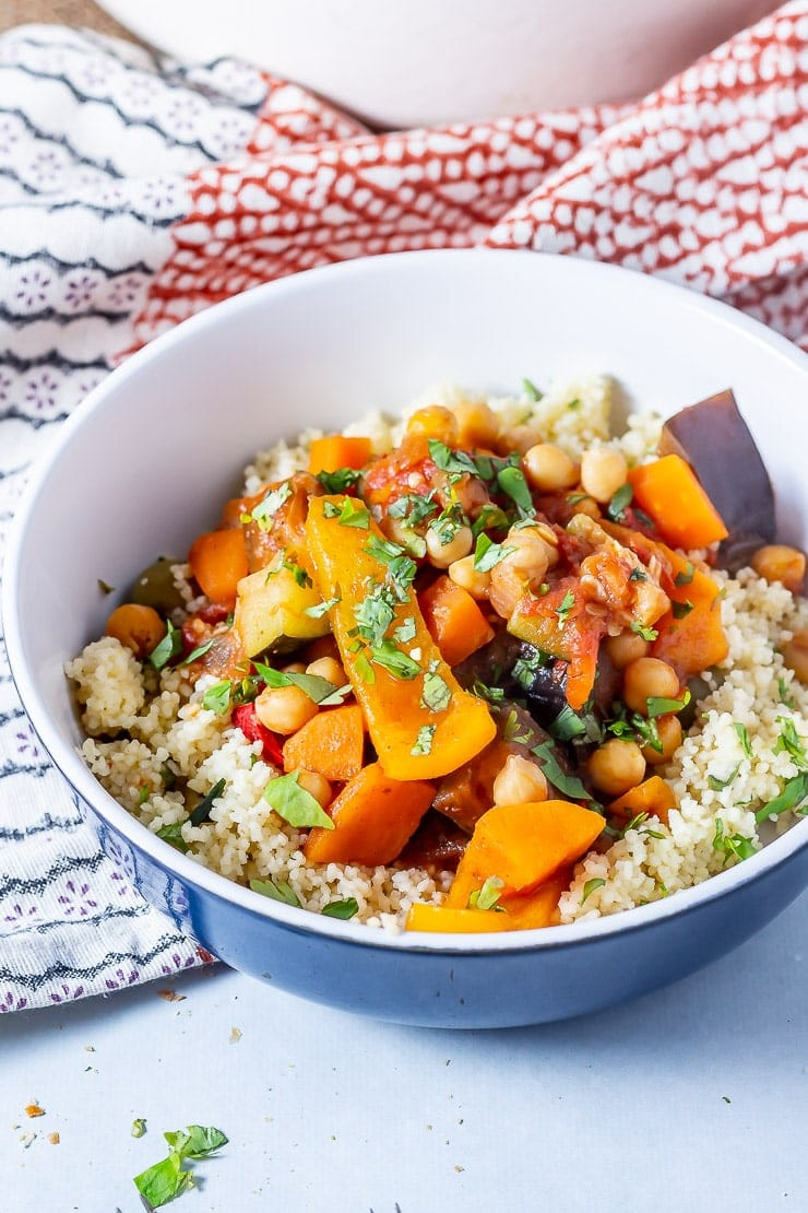 Side on shot of vegetable tagine with couscous in a blue bowl on a grey background