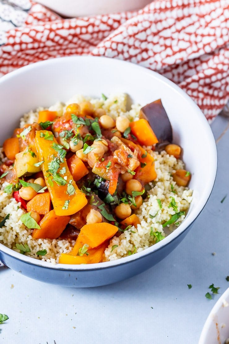 Side on shot of vegetable tagine with couscous in a blue bowl