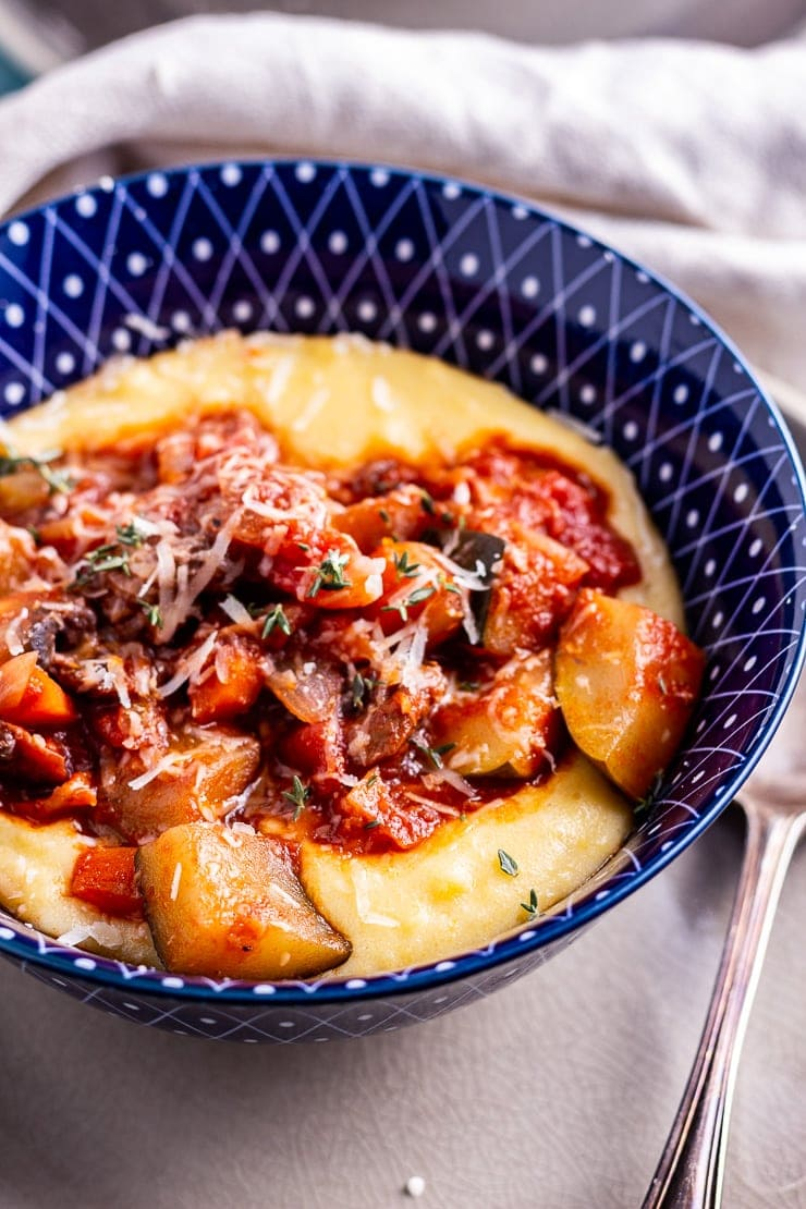 Close up of vegetable stew with creamy polenta in a blue bowl