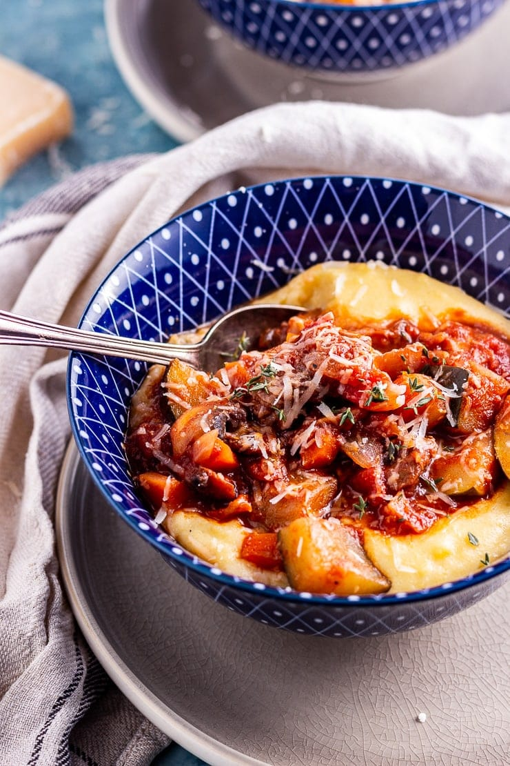 Close up of rich vegetable stew with creamy polenta in a blue bowl with a spoon