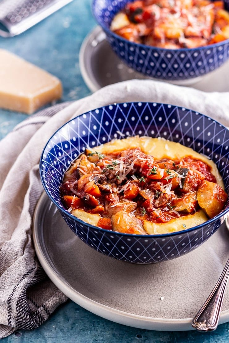 Side angle shot of vegetable stew with creamy polenta in a blue bowl with a spoon and cloth
