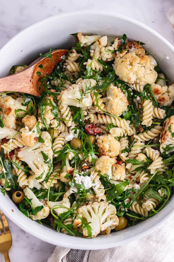 Overhead shot of roasted cauliflower pasta with a wooden spoon