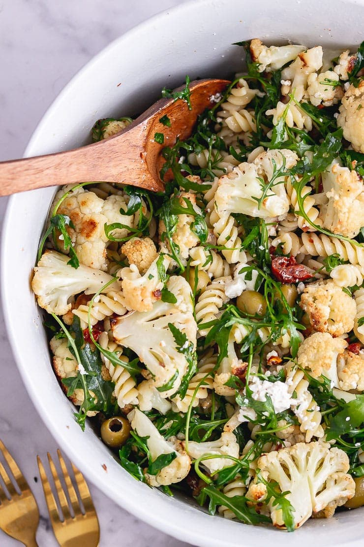 Overhead shot of roasted cauliflower pasta with a wooden spoon on a light background