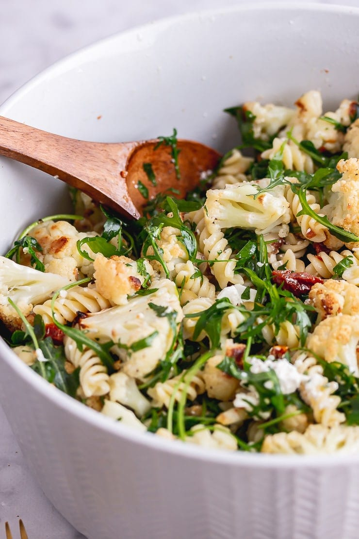 Side on shot of roasted cauliflower pasta with a wooden spoon in a grey bowl