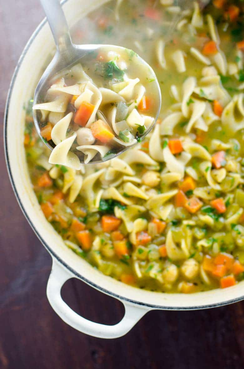 Overhead shot of chickpea noodle soup in a pot with a ladle from Umami Girl for vegan comfort food round up
