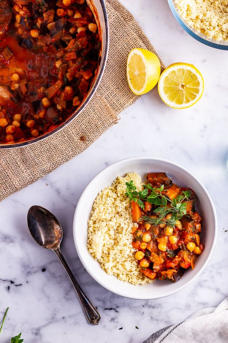 Overhead shot of harissa chickpea stew with couscous in a bowl on a marble background with lemon