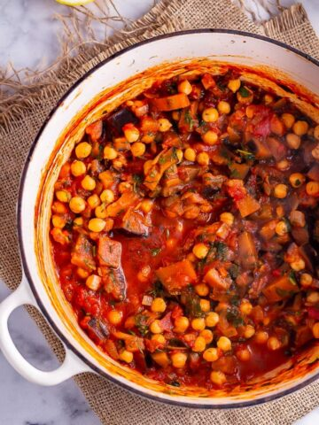 Overhead shot of harissa chickpea stew in a white pot on a woven mat
