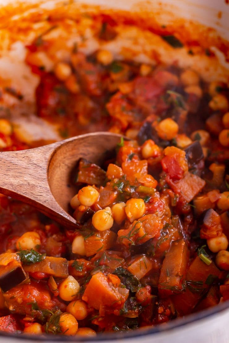 Close up of harissa chickpea stew with a wooden spoon in the pot