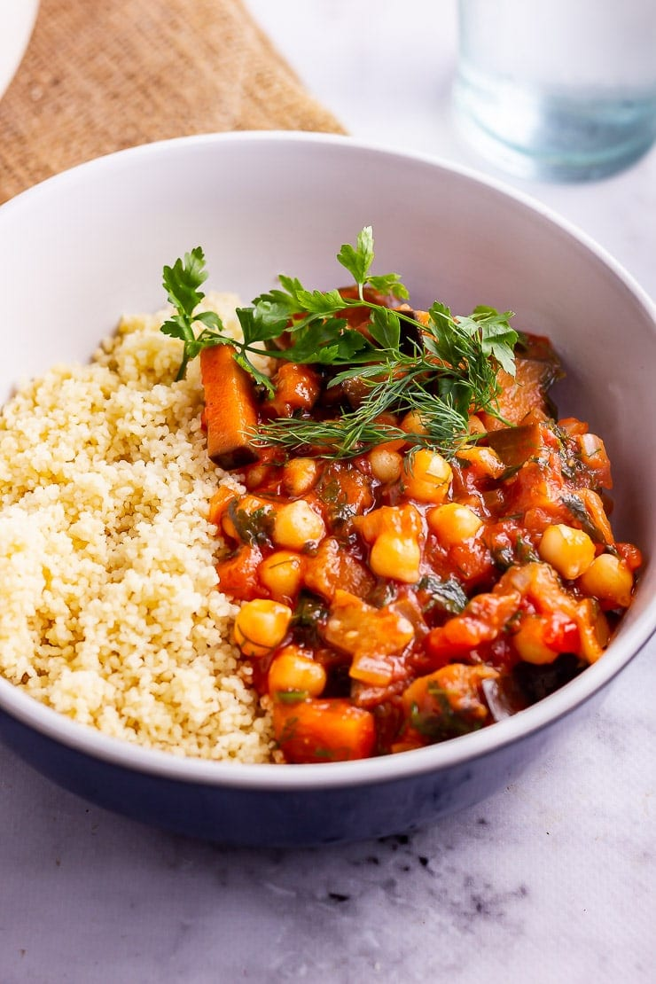Side on shot of harissa chickpea stew with couscous in a blue bowl