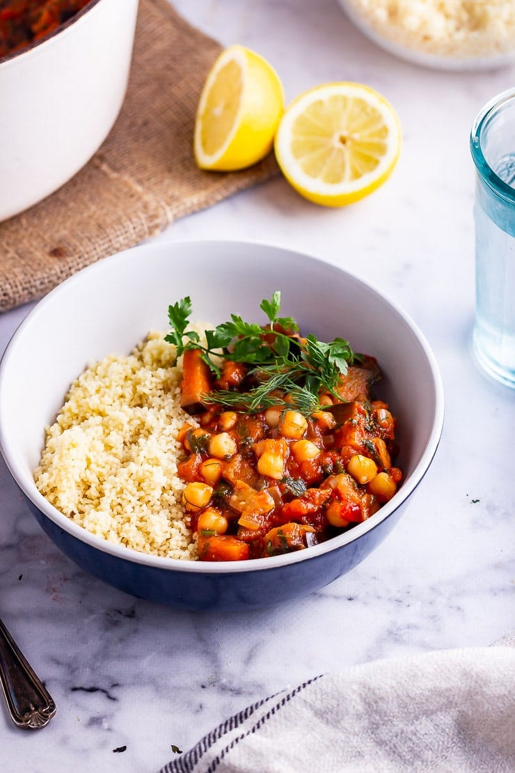 Harissa chickpea stew with couscous and herbs in a blue bowl on a marble background with lemon