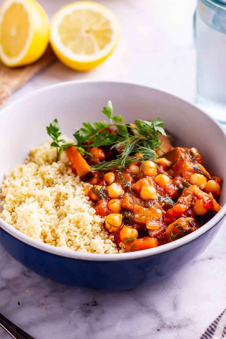 Side on shot of harissa chickpea stew with couscous and herbs in a blue bowl
