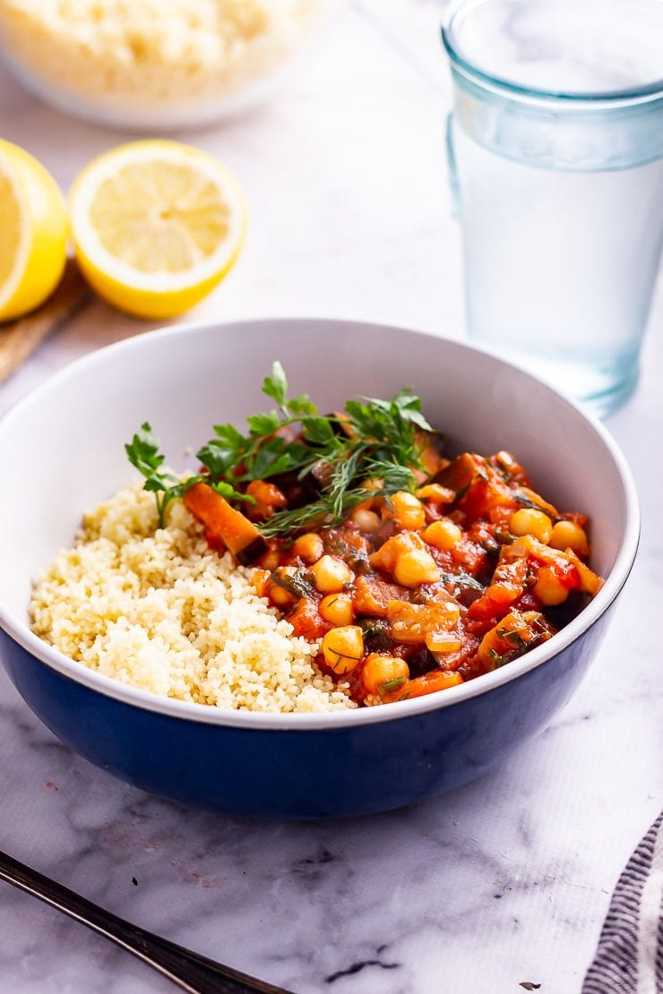 Side on shot of harissa chickpea stew with couscous in a blue bowl on a marble background