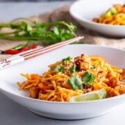 White bowl of spicy noodles with stir fried tofu on a grey surface
