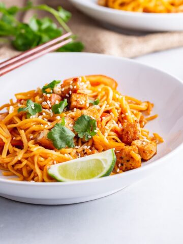 White bowl of spicy noodles with tofu, lime and chopsticks