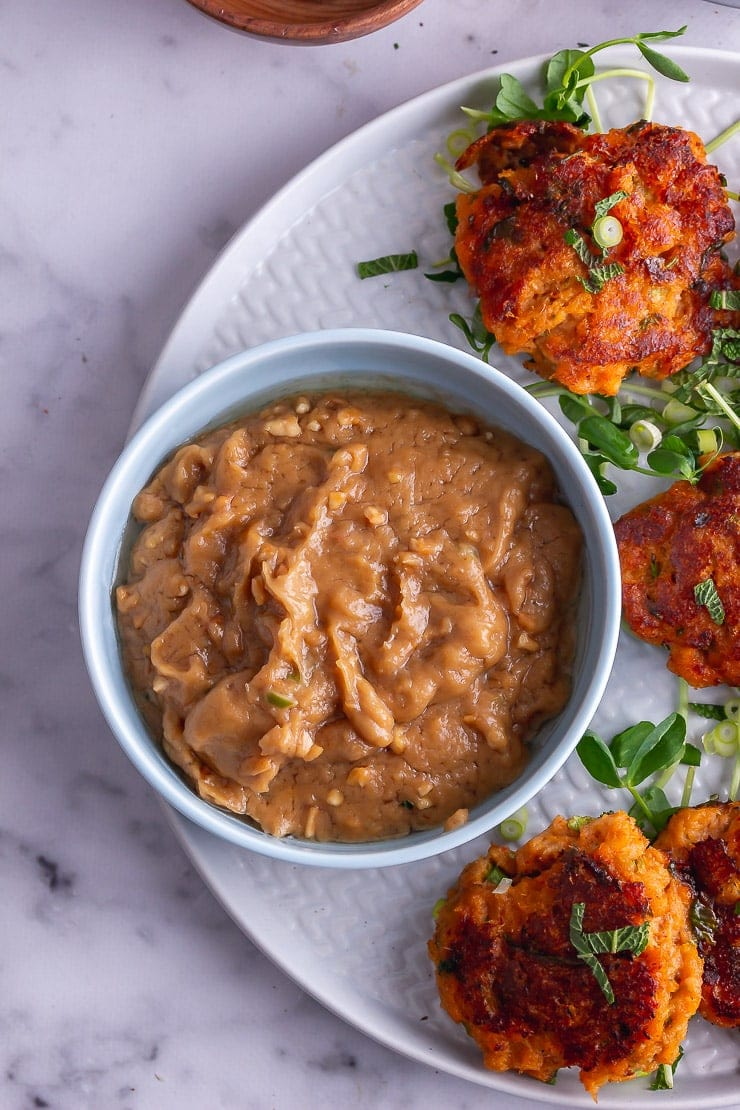 Overhead shot of peanut sauce in a blue bowl with Thai fish cakes