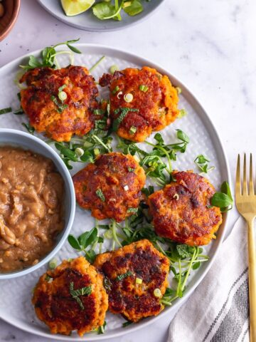 Overhead shot of Thai fish cakes on a platter with peanut sauce