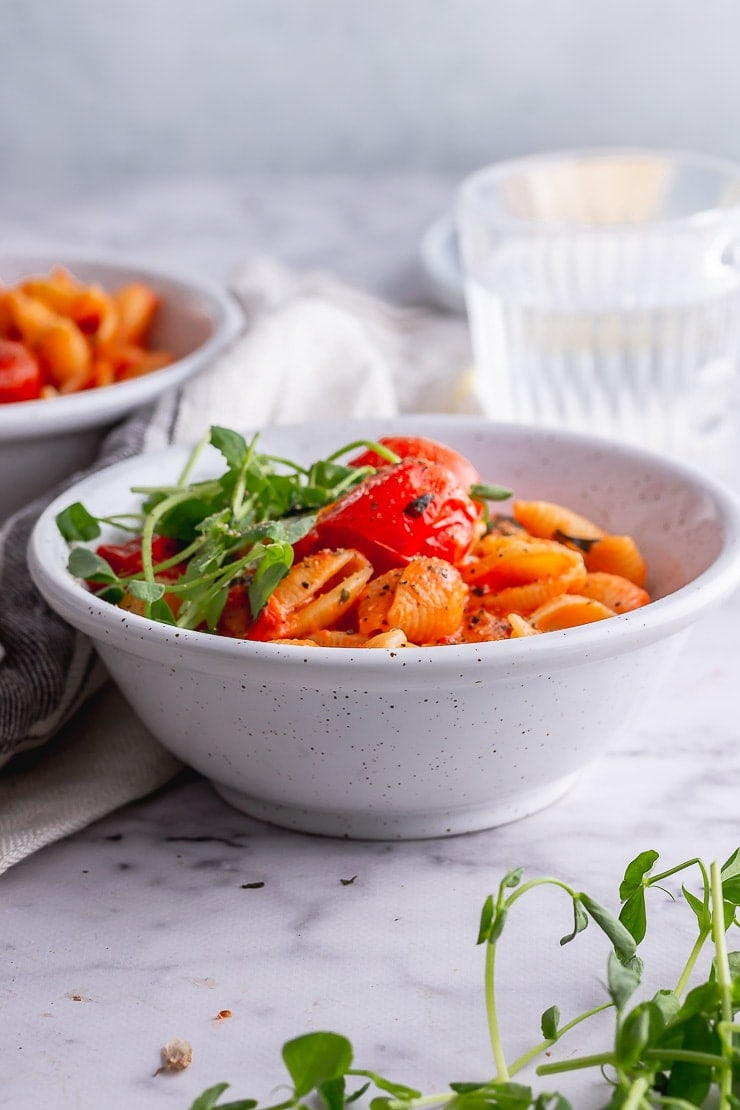 Side shot of tomato pasta in a white bowl on a marble background