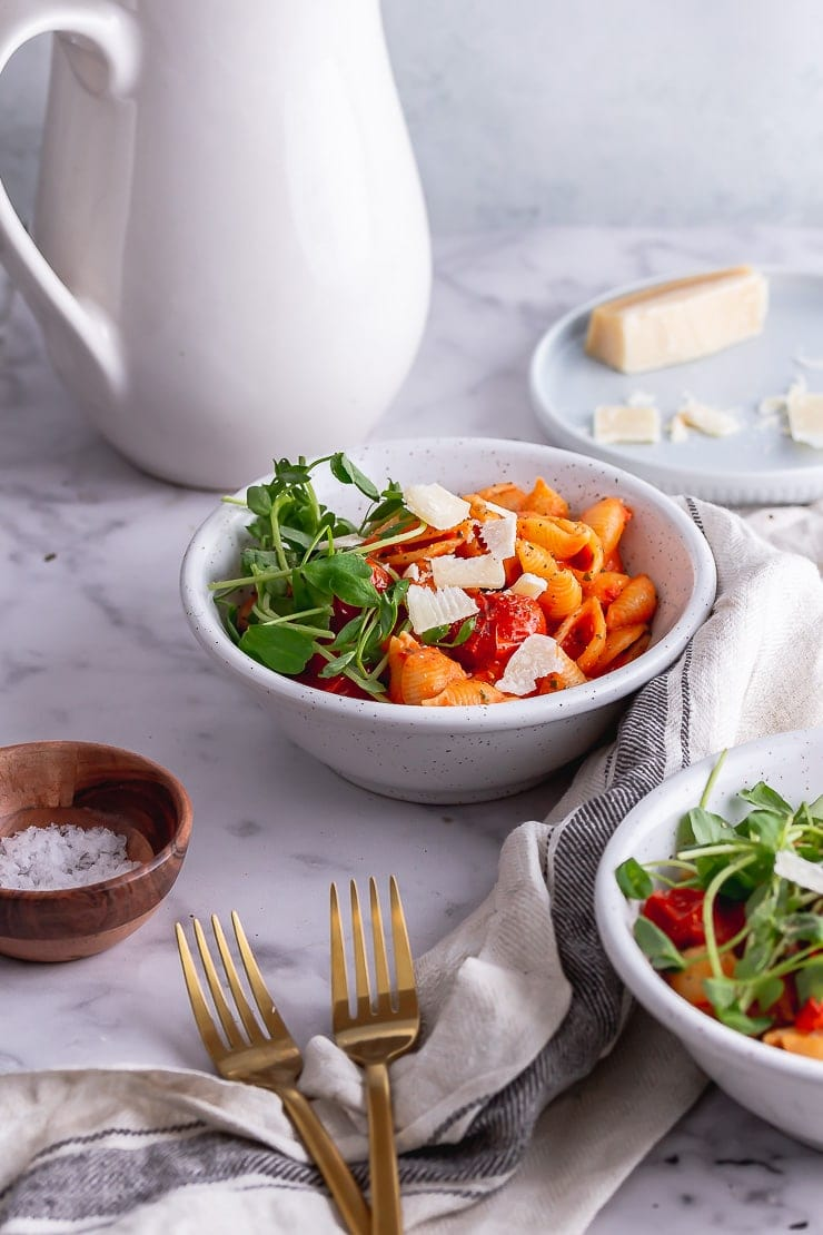 Side on shot of tomato pasta in white bowls with forks and a jug in the background