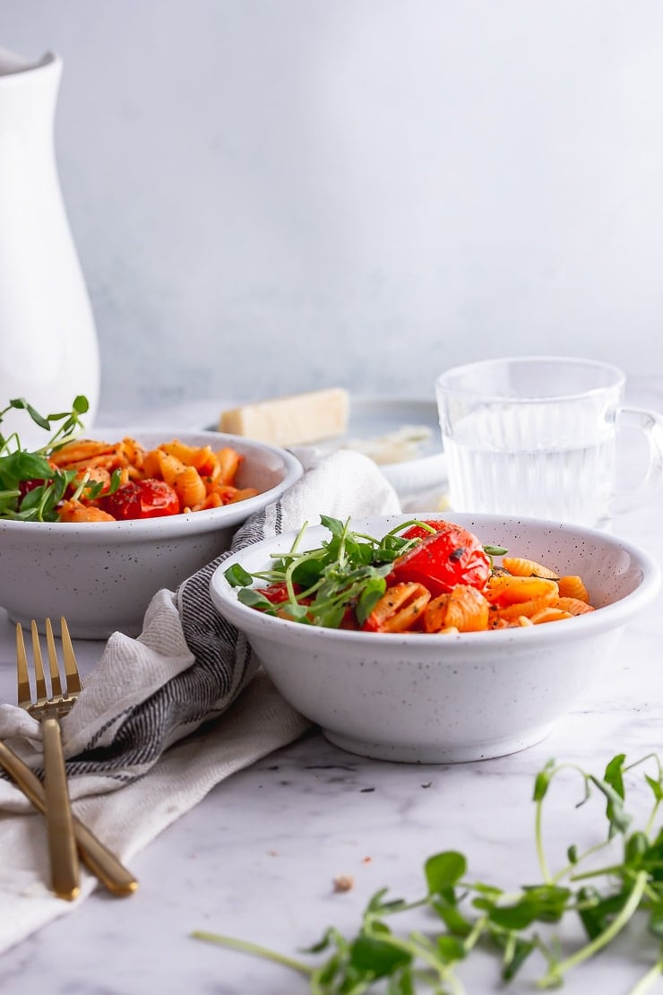 Side on shot of tomato pasta in white bowls on a marble background