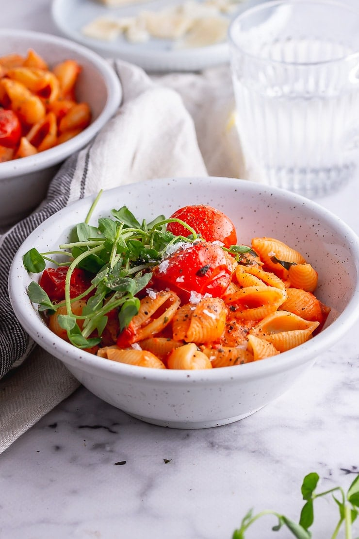 White bowl of tomato pasta with greens on a marble background