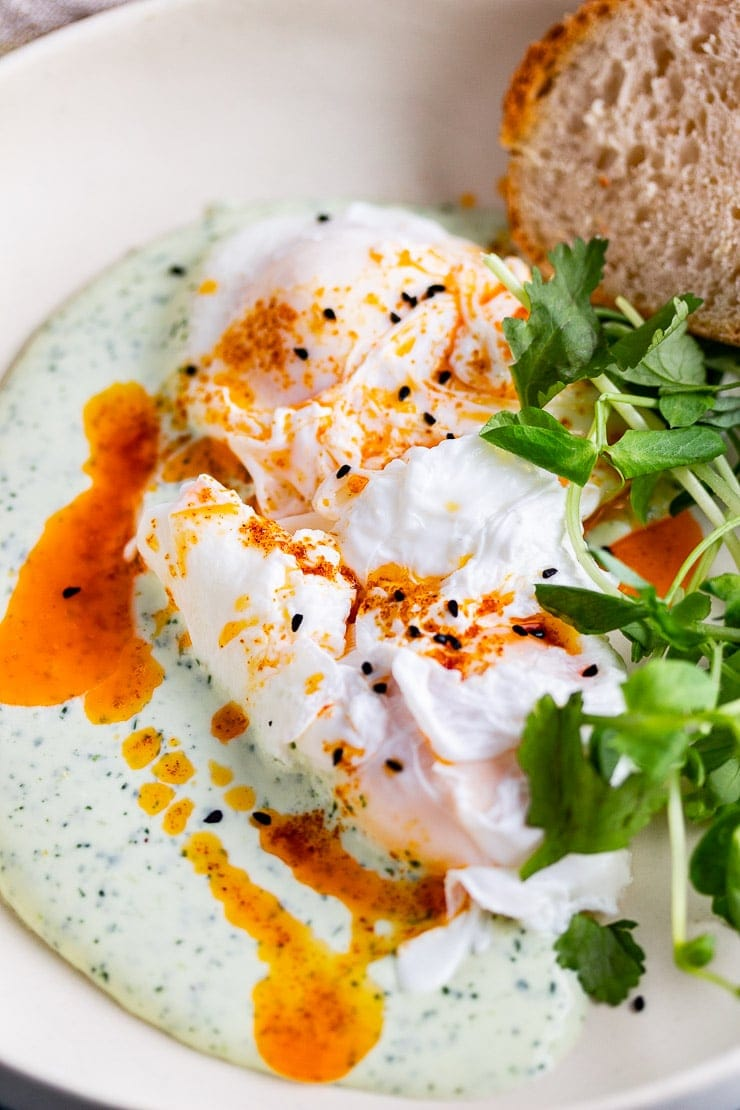 Close up of Turkish eggs with chilli butter and bread in a cream bowl