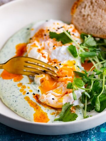 Turkish eggs with a fork breaking the yolk