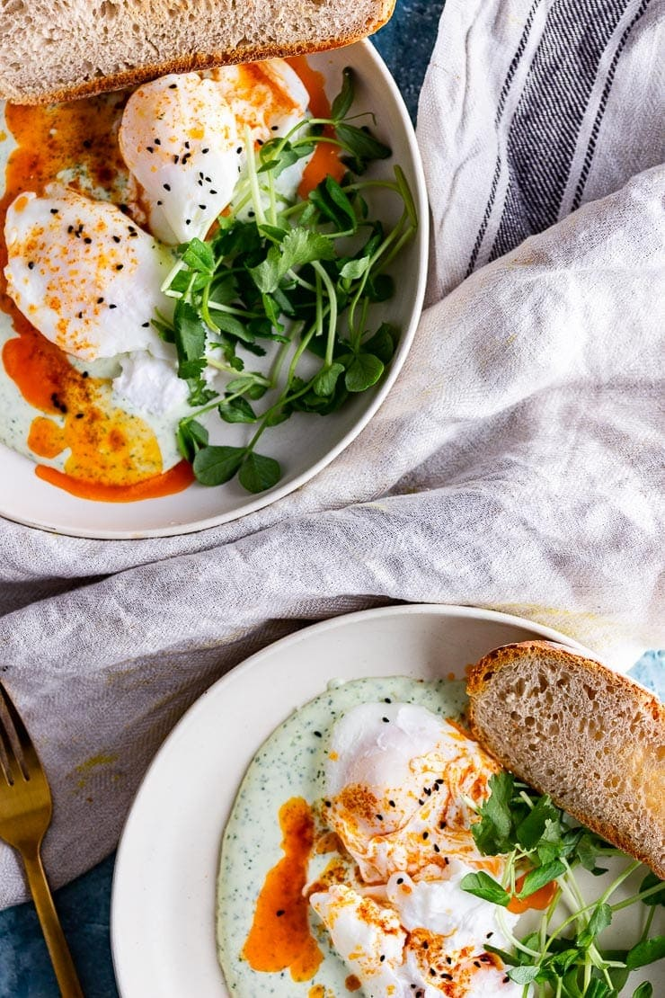 Two plates of Turkish eggs with bread and greens on a cloth
