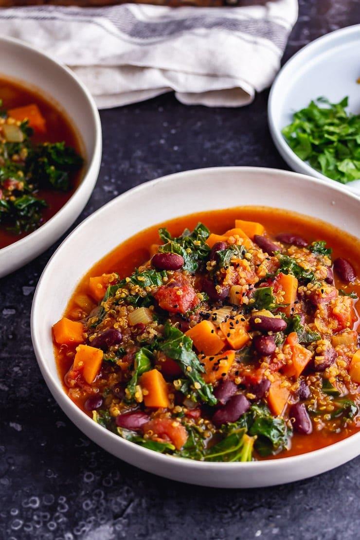 Vegan stew in a white bowl on a dark background