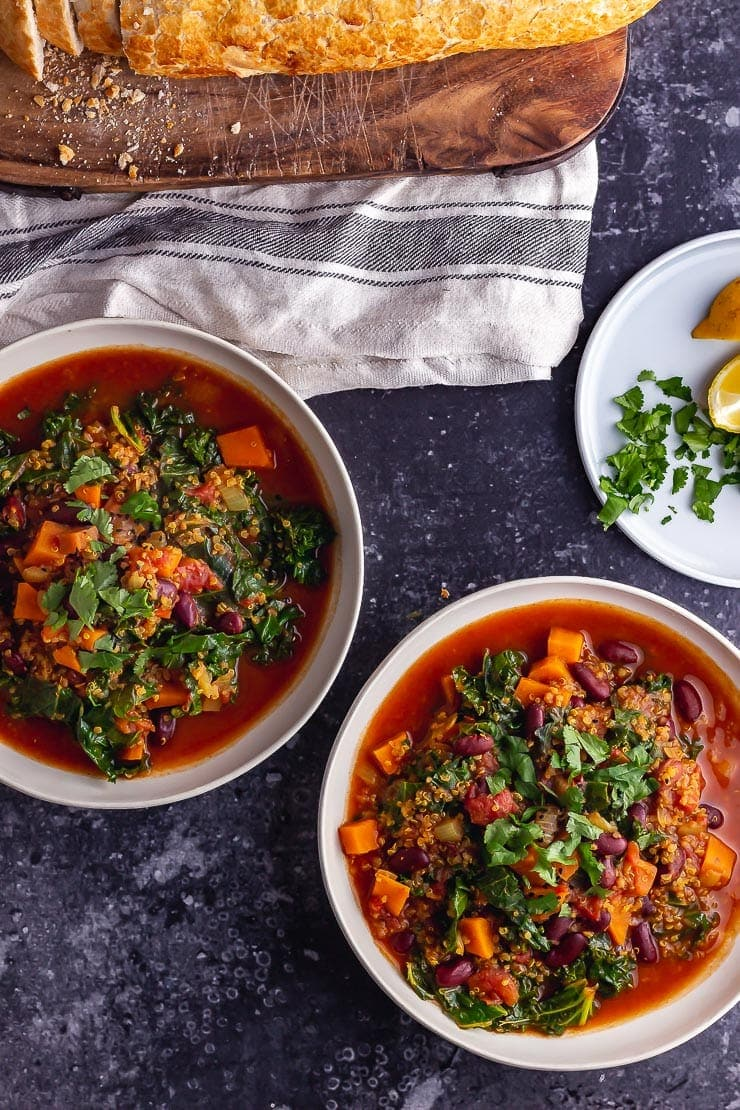 Two bowls of vegan stew on a dark background with bread