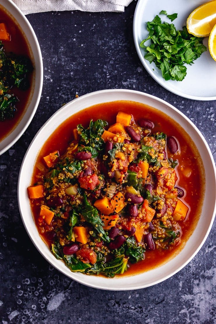 Overhead shot of a bowl of vegan stew on a dark background with lemon and herbs